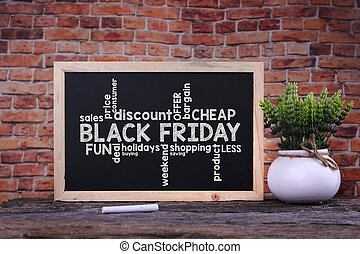 Black Friday word on blackboard with green plant.