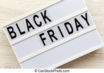 'Black Friday' word on lightbox over white wooden background, top view. Flat lay, overhead, from above.