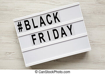 'Black friday' word on modern board over white wooden background, top view. Closeup.