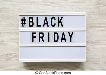 Black friday word on modern board over white wooden background, top view.