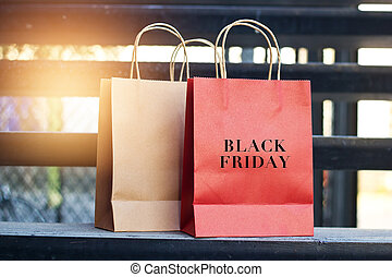 Black friday word on red and brown paper shopping bags placed on stairs outdoors on the mall background, business retail concept.