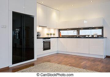 Black fridge in bright kitchen
