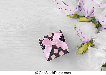 Black gift box with a pink bow and beautiful white eustoma flowers on a white wooden background top view