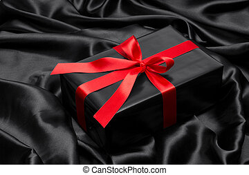 Black gift box with red satin ribbon and bow, over black satin