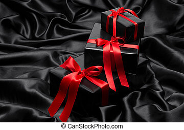 Black gift boxe with red satin ribbons and bows, over black satin