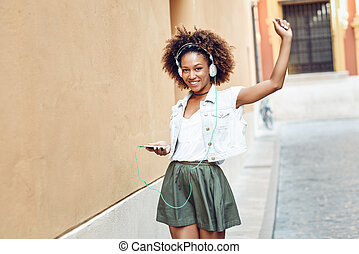 Black girl, afro hairstyle, in urban street with headphones and smartphone