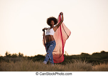 black girl dances outdoors in a meadow