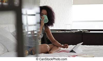 Black Girl Drinking Coffee And Studying In Bedroom At Home