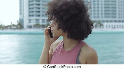 Black girl having phone call on seafront - Young casual...