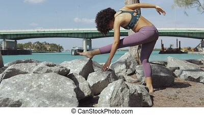 Black girl working out on riverbank - Side view of slim...
