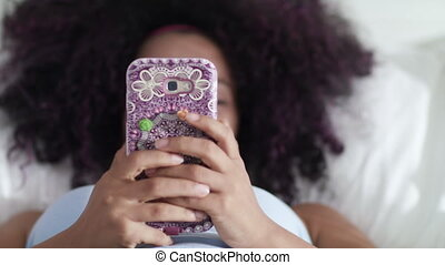 Black Girl Writing Love Message On Cell Phone In Bed - Young...
