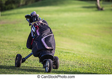 Black golf clubs drivers on green field