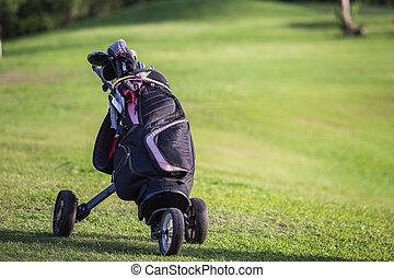Black golf clubs drivers on green field