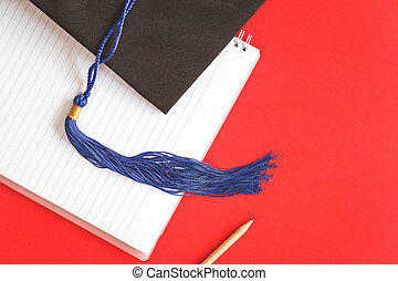 Black graduation cap with blue ribbon on red