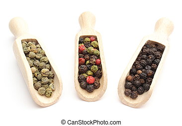 Black, green and colored pepper on wooden spoons