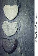 Black, grey, white zen hearts shaped rock on a tile background