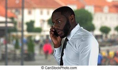 Black guy talking on phone.