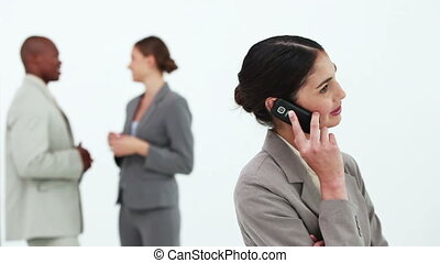 Black hair businesswoman on the phone with co-workers in...