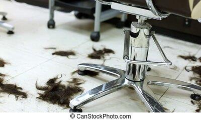 Black hair lie on floor in heap in hairdressing salon after...