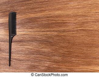 Black hairbrush hairdresser on shiny brown hair.