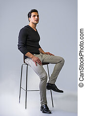 Black haired latino man sitting on stool - Brown eyed, black...
