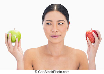 Black haired model holding apples in both hands looking at the green one on white background