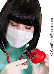 black-haired nurse with surgical mask using stethoscope on red heart