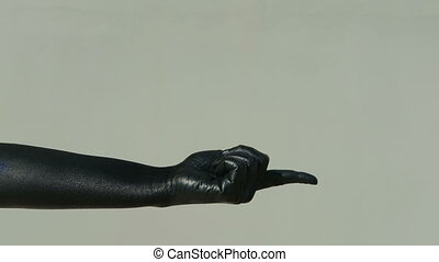 Black hand beckons with index finger against gray wall...