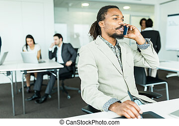 Black handsome graphics designer with dreadlocks using digitizer in a well lit, tidy office environment and talking on the phone while his colleagues are working hard in the background