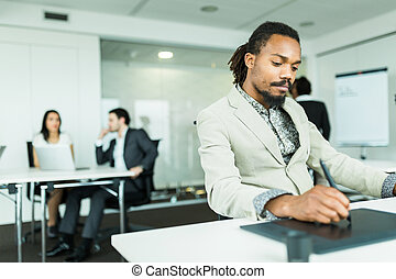 Black handsome graphics designer with dreadlocks using digitizer in a well lit, tidy office environment while his colleagues are working hard in the background
