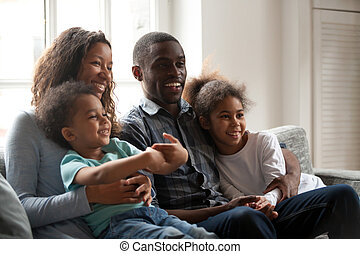 Black happy family together sitting on couch at home