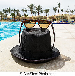 Black Hat with sunglasses around the pool at a resort