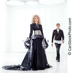 Black haute couture retro futurist couple in modern white hall with vampire inspiration
