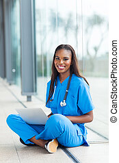 black healthcare worker using laptop