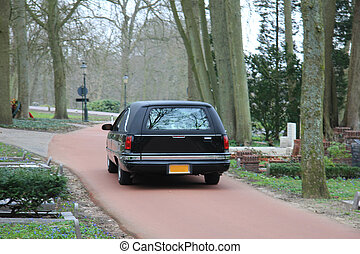 Black hearse on cemetary - A black hearse on a forest...