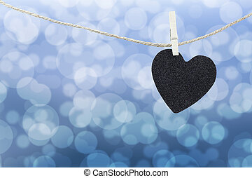 Black Heart hung on hemp rope on abstract colorful bokeh background.