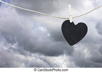 Black Heart paper hanging on a brown hemp rope on rain...