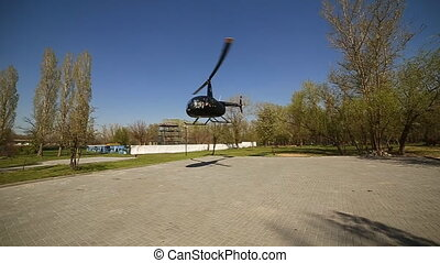 Black helicopter parked at airport tarmac.