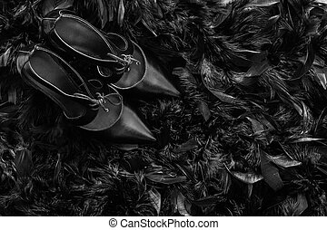Black high heel women shoes on black feathers   fur texture. Top view with copy space.