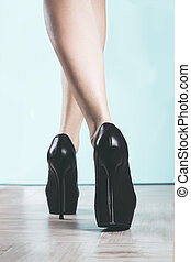 Black high heels shoes and long shapely legs.