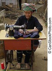 Black Hmong woman sewing machine - Black Hmong woman at her...