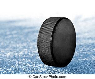 black hockey puck on ice rink