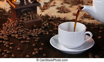 Black hot coffee poured into white cup from coffee pot,...