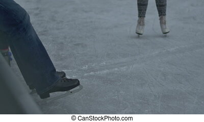Black Ice Skates - A man with black ice skates is resting on...