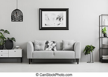 Black industrial bookcase and a plant stand next to an upholstered sofa in a gray living room interior with place for a coffee table. Real photo
