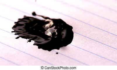 Black ink falling on lined paper in slow motion