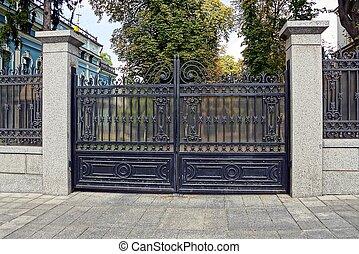 black iron closed gates on a concrete fence near the sidewalk