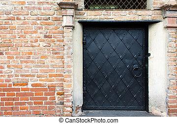 Black iron door in a brick wall