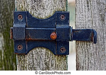 black iron latch on a wooden fence
