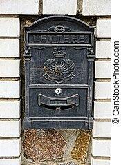 black iron mailbox on a brick wall